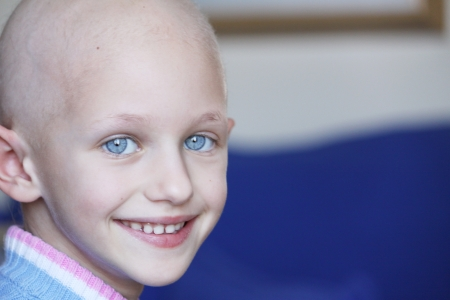 bald girl: a young caucasian child suffering hair loss due to the effects of chemotherapy used to fight cancer Stock Photo