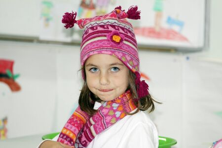a caucasian girl wrapped in a wooly hat and scarf  photo
