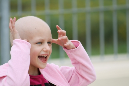 cancer patient: happy child who lost her hair due to chemotherapy to cure cancer