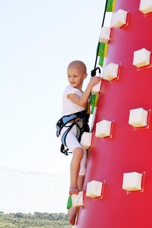 niño caucásico undergoin tratamiento para el cáncer de la escalada de un golpe hasta el castillo en un parque de atracciones
