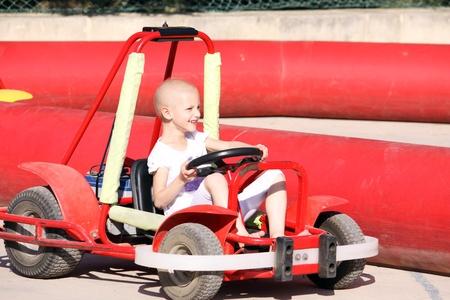 un niño caucásico experimentando Teatment el cáncer se divierten en un carro del ir en una feria