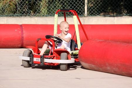 un bambino caucasico sottoposti a trattamento di chemioterapia per il cancro divertirsi su un carrello andare in un luna park Archivio Fotografico