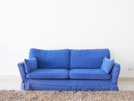 un sofá-cama doble azul sobre una pared en blanco Foto de archivo
