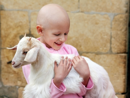 child with cancer carrying a goat Stock Photo