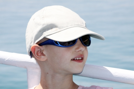 child with cancer wearing a cap and sunglasses