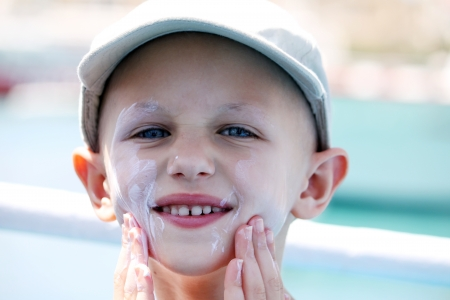leucemia: niño con cáncer se aplica protector solar