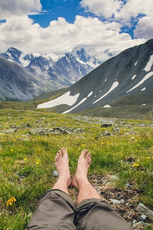 glaciers: Bare feet on a background of mountains, hills and glaciers