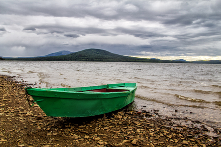 green boat: Green boat on the coast of lake mountain in bad weather Stock Photo