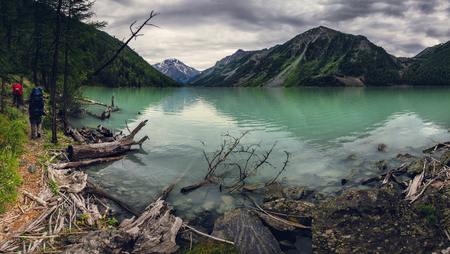 range of motion: Group of hikers traveling along the shore of green lake in Altai mountains Stock Photo