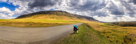 illuminate: Panorama of the hill, paved road and parked bike Stock Photo