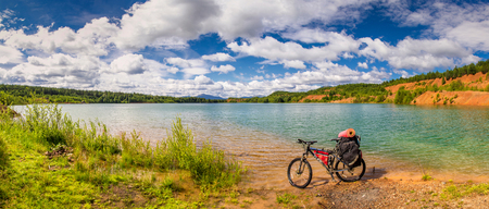 illuminate: Panorama of blue lake, lake shore and parked touring bike Stock Photo