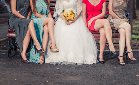bridesmaids: The legs of the bridesmaids sitting on the bench
