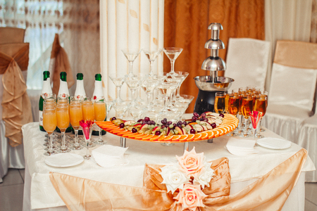 wine and dine: Decorated table for a festive Banquet, with drinks and fruits Stock Photo