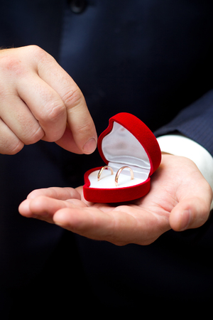 lend a hand: Gold wedding rings in box on grooms palm Stock Photo