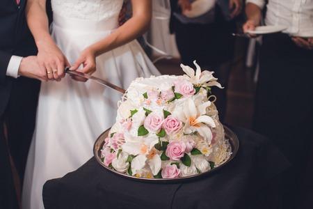 Newlyweds cutting delicious unusual wedding cake Stock Photo