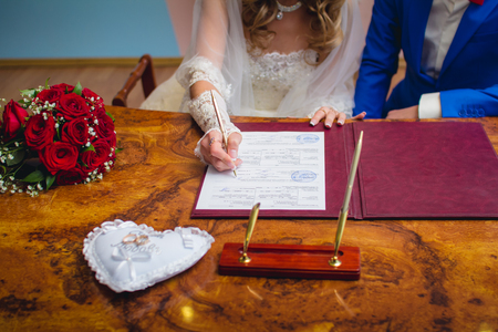 wedlock: Bride signing marriage license or wedding contract Stock Photo