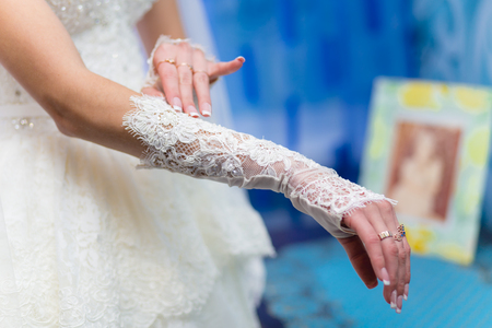 lace gloves: Hands of the bride with lace gloves and precious rings Stock Photo