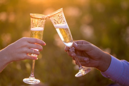 Glasses of champagne on a background of pale pink sunset sky