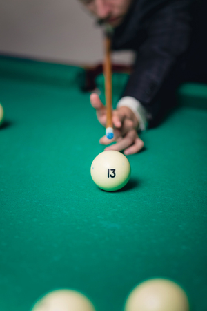 billiards rooms: A Billiards player strikes the ball number 13 Stock Photo
