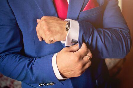 cufflink: Elegant mans hand adjusting the cufflink