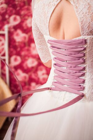 lace up: Bride lace up corset wedding dress. Rear view Stock Photo