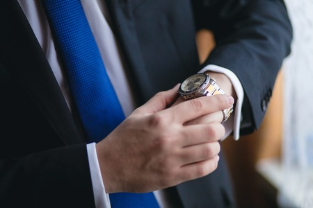 tardy: Businessman looking at his watch