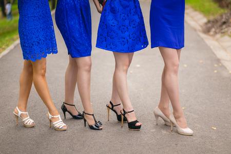 bridesmaids: Girls bridesmaids legs in blue dresses outdoors