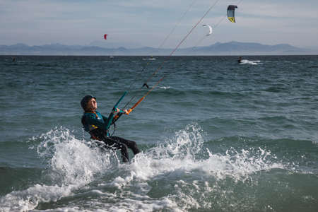 Teenager is practicing kitesurf. She is trying to control the kite.