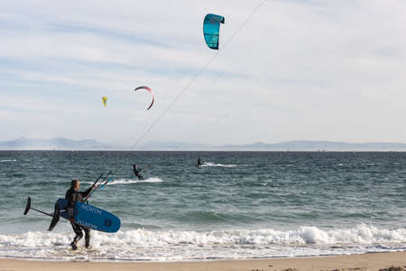 Man is practicing kitesurf in the sea. He is going to ride waves.
