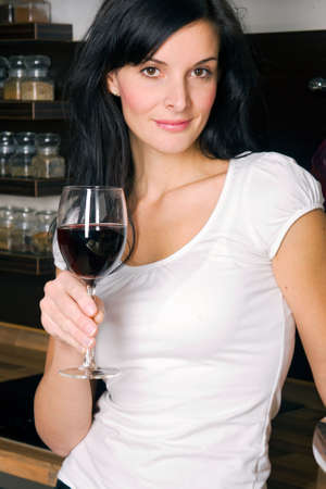 Woman drinking wine in kitchen