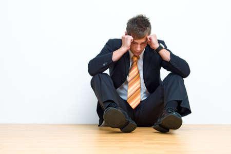 Unhappy businessman sitting on floor photo