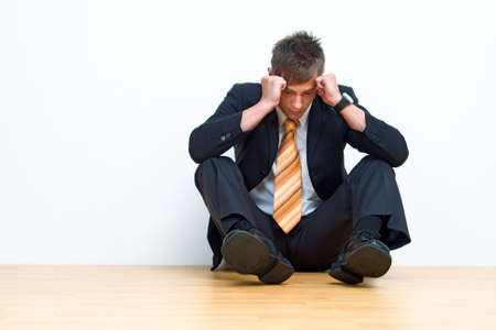 Unhappy businessman sitting on floor Stock Photo