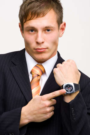 Angry young businessman showing his watch