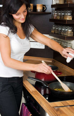cravings: Young woman preparing lunch in kitchen Stock Photo