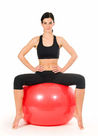 Brunette woman excercising with a pilates ball - studio shot photo