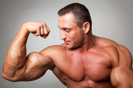 Muscular man flexing his biceps on gray background Stock Photo - 5341282