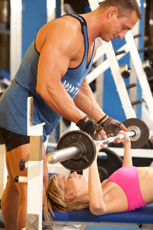 Woman and her trainer doing exercise at the gym Stock Photo - 5341281