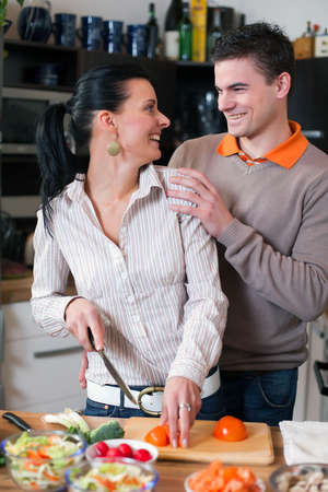 Young couple preparing lunch in kitchen photo