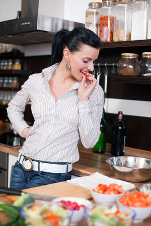 Beautiful young woman making and tasting vegetable salad Stock Photo - 5341234