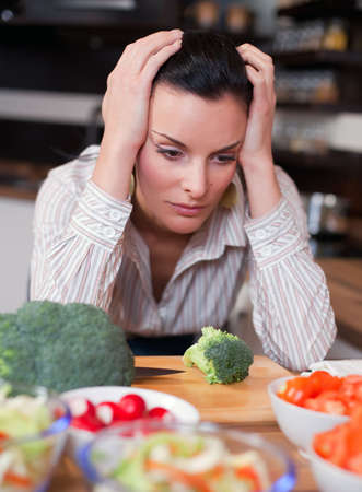 Depressed and sad woman in kitchen photo