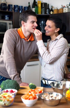 Young couple making and tasting vegetable salad photo