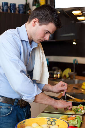 Young man preparing lunch in kitchen Фото со стока