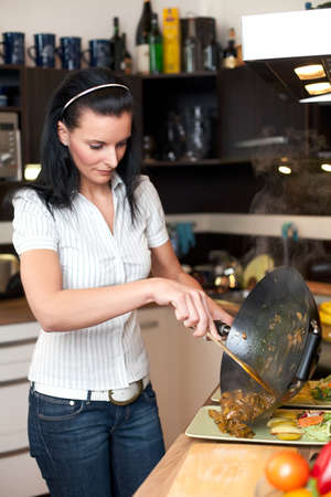 fryingpan: Young attractive woman preparing lunch in kitchen