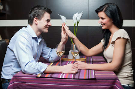 Attractive couple drinking wine and flirting photo