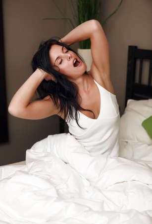 Beautiful young woman yawning in bed