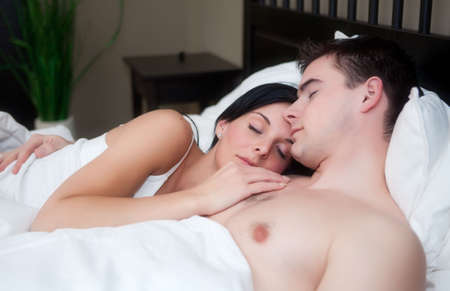 Brunette young girl sleeping with a boy in bed Stock Photo