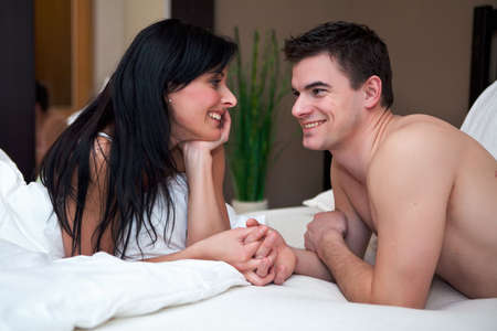 Young attractive happy couple in bed
