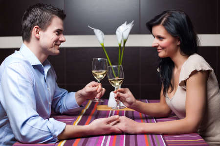 Attractive young couple drinking wine and flirting Stock Photo