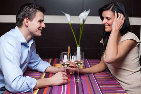 Attractive young couple drinking wine and flirting photo