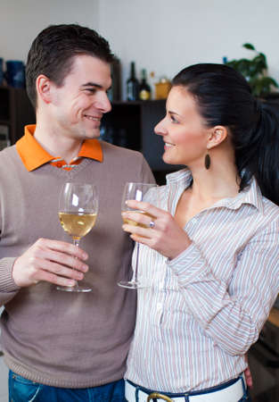 Young couple drinking vine in kitchen photo